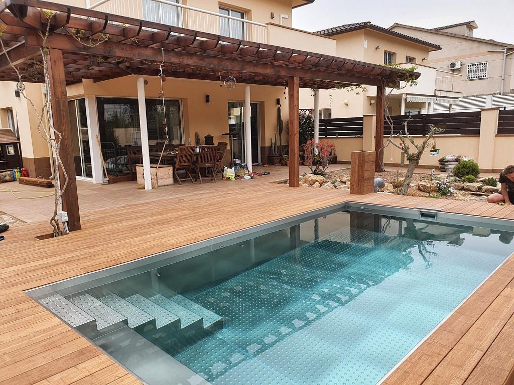 Piscina de acero inoxidable con escalera interior y banco con tarima de madera de bambú